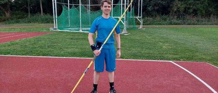 Sebastian Fenn trägt Schweißbänder mit Sensoren und einen Speer.